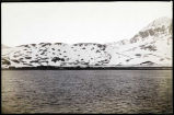 [View from water of row of buildings on shoreline in front of snow-covered hills, mountains to...