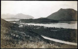 [View from hillside of town along banks of a channel, hills and mountain opposite, mountains...