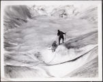 [Father Hubbard pulling dog up an ice ledge on glacier.]