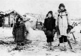 Three native children, standing in front of log cabin dressed in winter clothing.