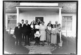 [Group of people, with decorated cake, in front of mission house.]