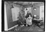 [Family-group by Christmas tree in home.]