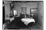 [Interior shot of dining room. Man sitting at the table, cracking nuts. Stuffed owl decorates...
