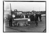 [Funeral on cannery dock. Group of people standing behind coffin.]