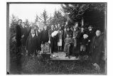 [Funeral in the wood before ANB Hall was built.  Group of people surrounding decorated coffin.]