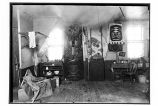 [Interior view of a room, with several native artifacts, including a house pole.]