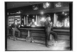 [Interior view of bar with two bartenders behind the bar and two men at the bar. (Juneau? Red Dog?...