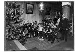 [Group portrait of children by Christmas tree.]