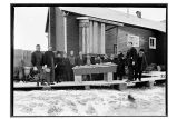 [Funeral group standing around casket on wooden sidewalk.]