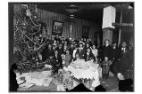 [Group portrait by Christmas tree, with gifts piled in foreground.]