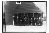 [Eight men and one child standing in front of fox pelts hung on the wall of building.]