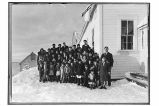 [Group of children and adults standing outside of school next to ANB Hall.]