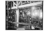 [Interior shot showing men and feeding machine at the cannery.]