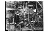 [Interior view of the cannery showing men and the feeding machine.]