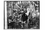 [Interior shot of men and machinery in the cannery.]