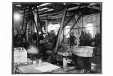[Interior view of the cannery showing men and machinery.]