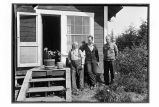 [Three men standing by steps of house. Two potted plants are on the top step.]