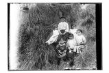 [Group of six children sitting in grass.]