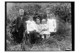 [Woman and five children sitting in grass.]