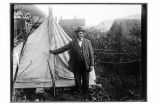 [Man standing in front of tent. Garden and buildings in the background.]
