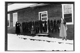 [Mrs. Bob Roland, two children, and Mrs. Joe Arrington standing in front of the mess hall. Fox...