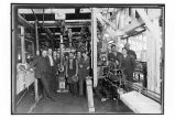 [Interior view of cannery, showing group of workers by machinery.]