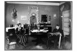[Interior view of a home, with man reading paper and woman sewing.]