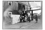 [Cannery worker bringing boxes of canned salmon out of the storehouse for loading on the steamer.]
