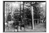 [Interior view of the cannery, with men working at machines.]