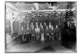 [Interior view of the cannery, with men assembled for group portrait.]