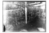 [Interior view of the cannery, with machines and workers.]