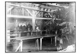 [Interior view of the cannery, with workers at the machines.]