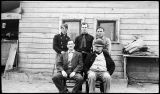 [Five men sit outside wooden building.]