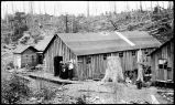 [A man with three women stand on boardwalk outside cabin. Man with apron stands outside another...