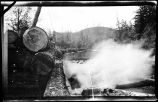 [End of log and steam visible in foreground with river and mountains in background?]