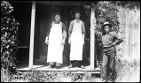 [Two men in aprons stand on porch, third man with pipe leans against pole.]