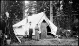 [Family stands outside tent. Couple with small child standing in a wagon outside a tent. Tent in...