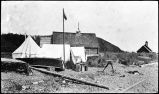 [Three surveyor's tents, flagpole, and survey tripod beside two cabin structures on beach with...