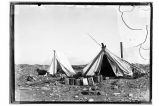 [Two tents with oil cans in front.]
