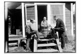 [Three men gathered around two potted plants on steps of a house.]