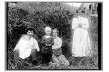 [Two women, a man, child, and infant sitting or standing in overgrown yard.]