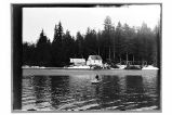 [View, over water, of house and cabin; forest in background; man in rowboat.]