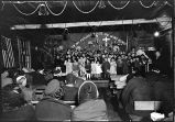 [Christmas time; children, of various ages, on stage performing for audience sitting on benches.]