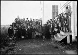 [Children, of various ages, standing for group portrait outside of school house.]