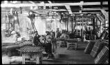 [Interior view of the cannery, showing men and machines.]