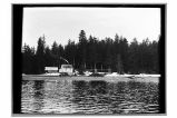 [View, over water, of house and cabin, forest in background.]