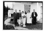 [Six member wedding party standing in front of house.]