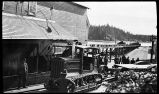 [A Holt tractor pulling flatbed car down railroad tracks in Yakutat.]