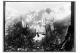 [Two men standing, woman and Native child sitting in shrubbery; mountain in background.]