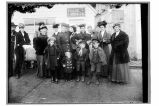 [Group of men, women, and children standing outside of Peniel Mission building; three holding...